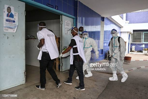 Two agents of the National Institute of Public Hygiene wearing personal protective equipment suits against the Ebola virus arrive at the CHU of...