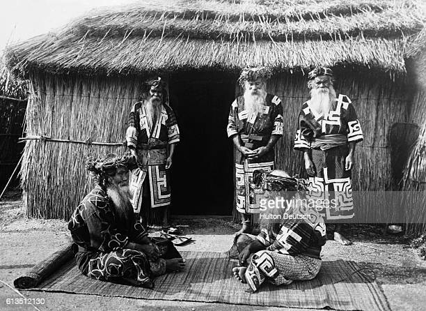 Two Ainu tribesmen discuss business outside a village hut with three neighbors standing nearby as witnesses | Location Northern Japan