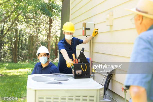 two air conditioner workers service outside unit. - air conditioner stock pictures, royalty-free photos & images