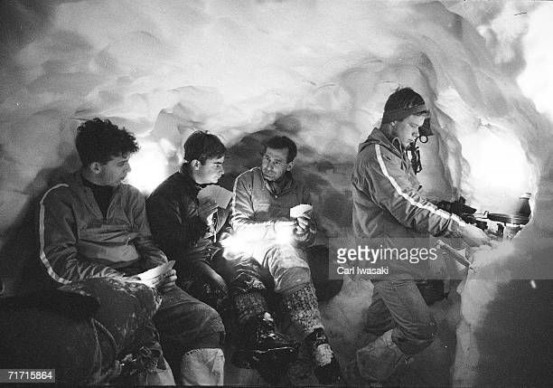 Two Air Force Academy cadets play cards with their instructor in a snow cave while a third cadet cooks over a camp stove on a ledge in the cave near...