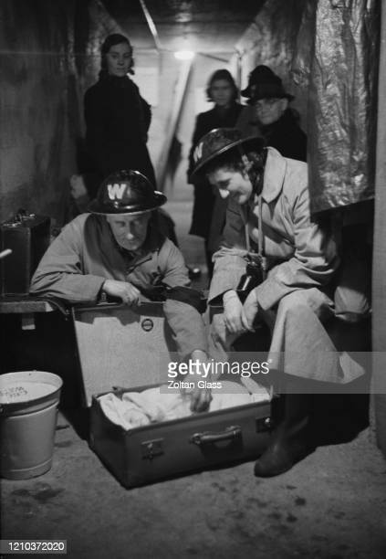 Two Air Raid Wardens tending to a baby in a suitcase at an air raid shelter in London during the Blitz October 1940 Original Publication Picture Post...