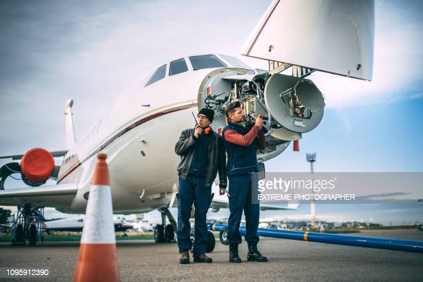 two aircraft engineers working on a sensor array in the nose cone of an airplane parked outside on a tarmac - sensor stock pictures, royalty-free photos & images