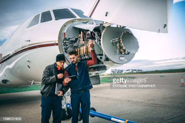 Two aircraft engineers working on a sensor array under the nose cone of a private jet parked on an airport tarmac