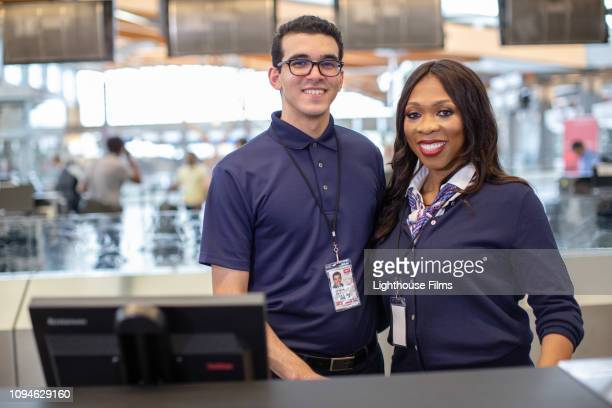 Two airline employees smile at camera at airport check in counter.