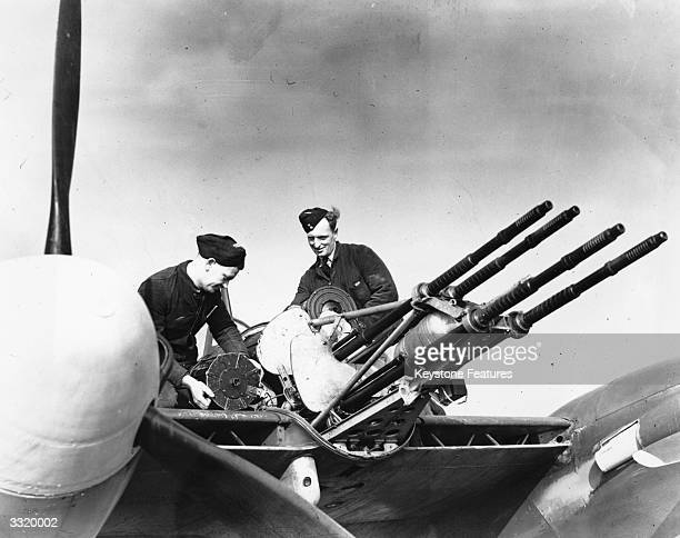 Two airmen loading ammunition onto a Westland Whirlwind or 'Whirlibomber' The fighterbomber plane has four Hispano 20mm guns each of which carry a...