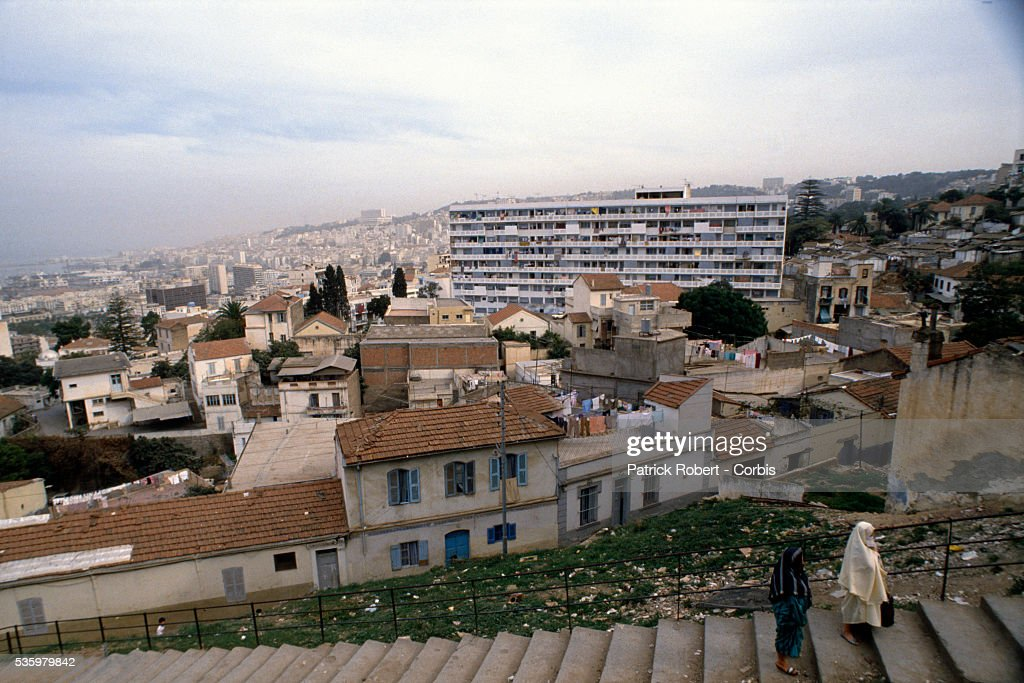 Two Algerian women walk up a stairway near houses and apartments in Algiers.