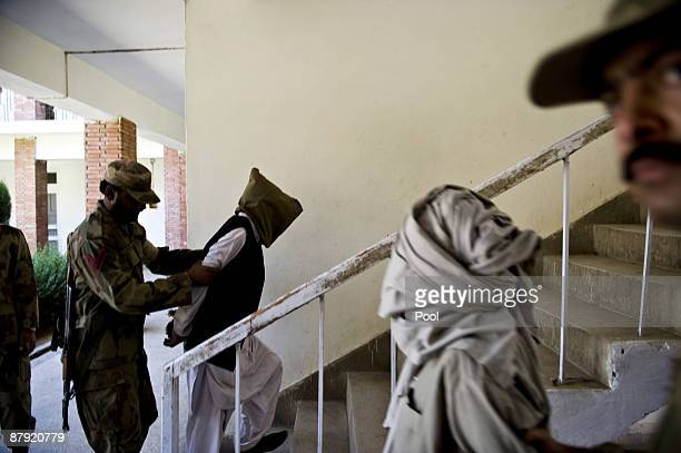 Two alleged Taliban militants are escorted by soldiers after been presented to journalists inside an army base on May 22 2009 in Khwazakhela Pakistan...