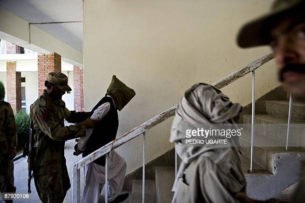 Two alleged Taliban militants are escorted by soldiers after being presented to journalists inside an army base in Khwazakhela on May 22 2009 Two...