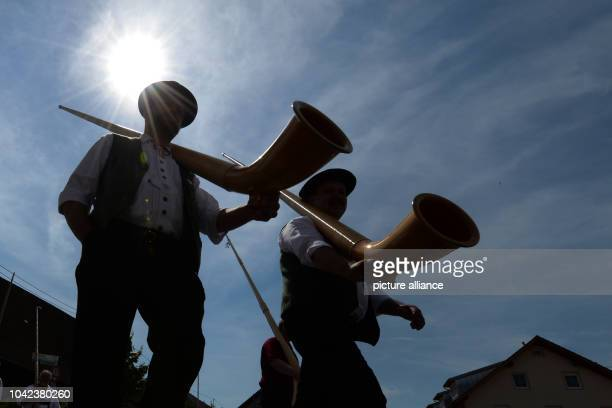 Two alphorn players carry their alphorns on their shoulders at the 39th BadenWuerttemberg Alphorn Meeting in Roetenbach Im Allgaeu Germany 18 August...