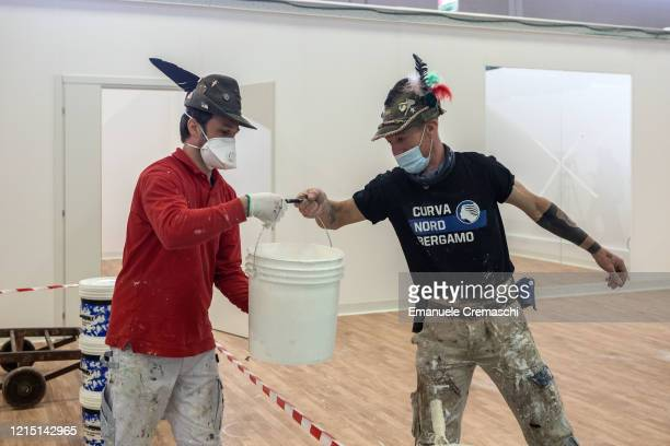 Two Alpini veterans work at the building site of a field hospital inside the Bergamo Exhibition Center on March 27 2020 in Bergamo near Milan Italy...