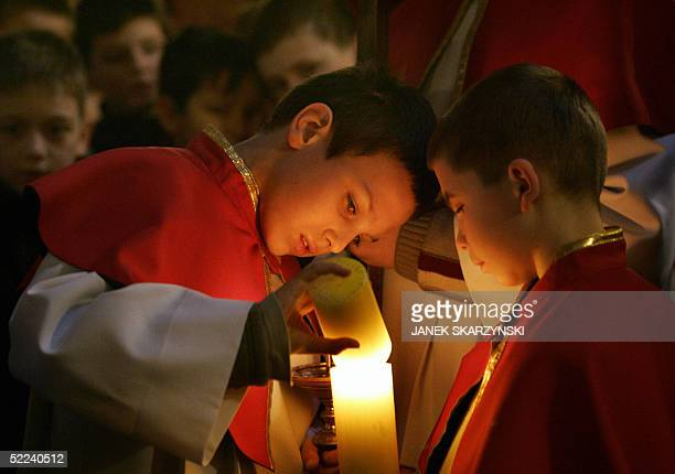 Two altarboys ligh a candle during a holy mass dedicated to Pope John Paul II in a church of Wadowice the home town of the Pope 25 February 2005...