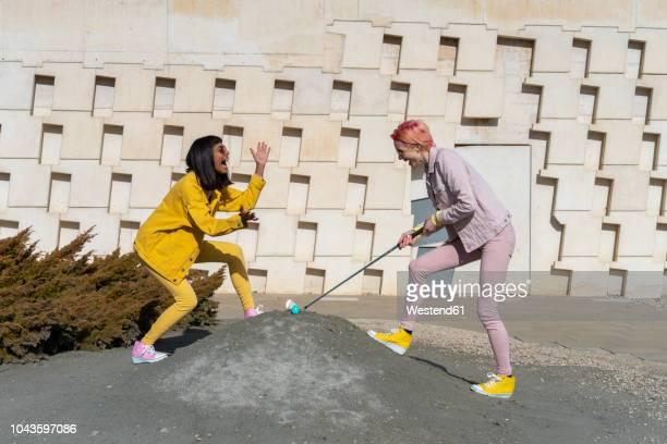 two alternative friends golfing - irony stockfoto's en -beelden