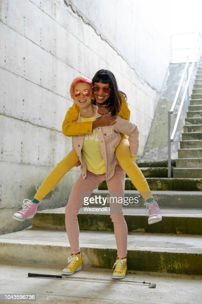 two alternative friends having fun, wearing yellow and pink jeans clothes - piggyback stock pictures, royalty-free photos & images