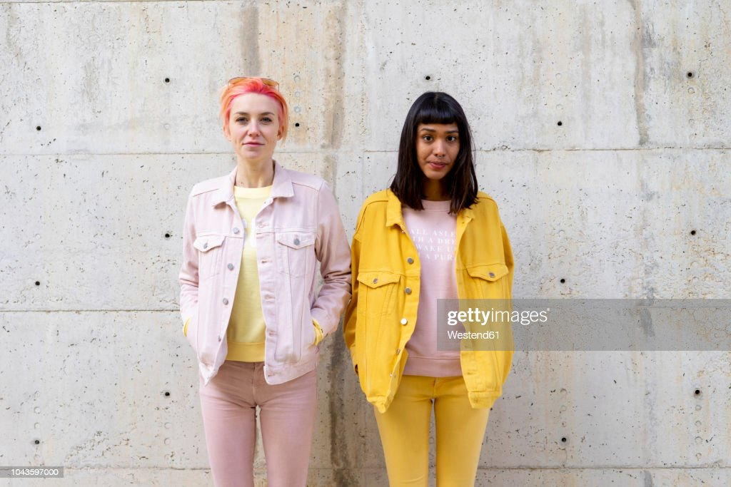 Two alternative friends having fun, wearing yellow and pink jeans clothes : Stock Photo