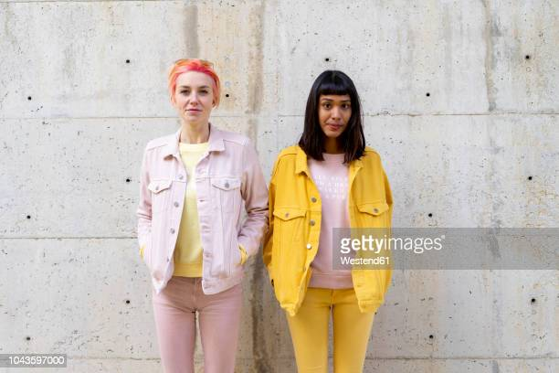 two alternative friends having fun, wearing yellow and pink jeans clothes - due persone foto e immagini stock