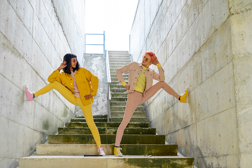 Two alternative friends posing on steps, wearing yellow and pink jeans clothes - gettyimageskorea