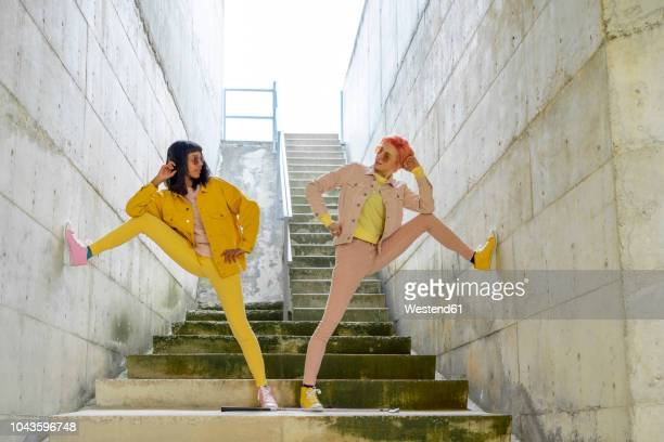 two alternative friends posing on steps, wearing yellow and pink jeans clothes - opstand stockfoto's en -beelden