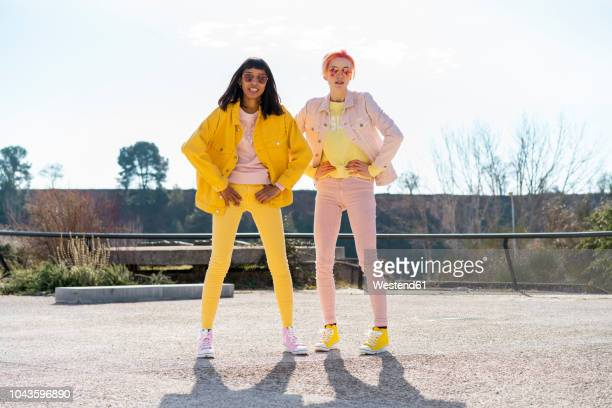 two alternative friends wearing yellow and pink jeans clothes, posing - yellow shoe stock pictures, royalty-free photos & images