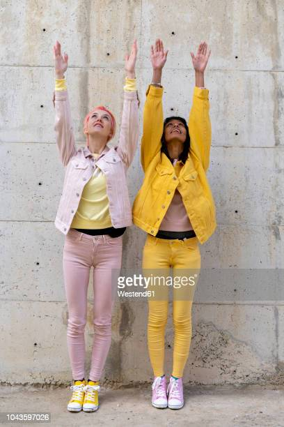 two alternative friends wearing yellow and pink jeans clothes, posing, raising arms - yellow shoe stock pictures, royalty-free photos & images