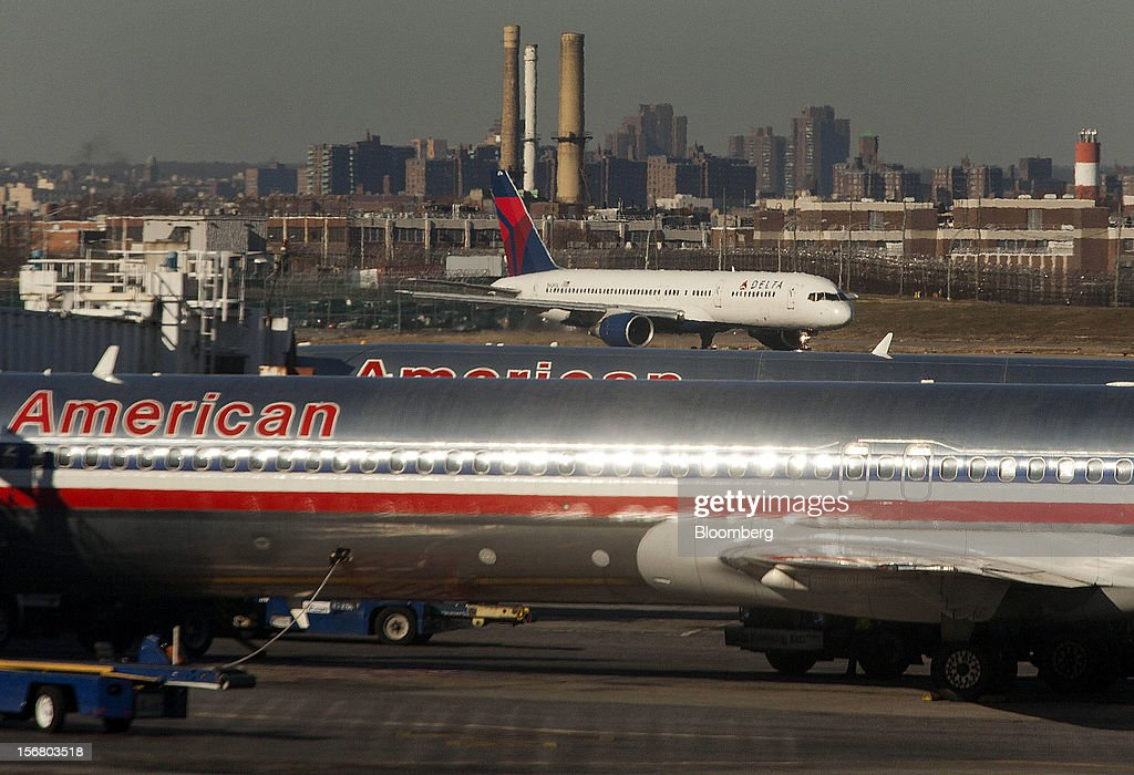 Two American Airlines Inc. jets sit parked at gates while a Delta Air Lines Inc. plane taxis down the runway at LaGuardia Airport in the Queens borough of New York, U.S., on Wednesday, Nov. 21, 2012. U.S. travel during the Thanksgiving holiday weekend will rise a fourth straight year, gaining 0.7 percent from 2011, as trips by automobile rise even as airplane trips decline, AAA said last week. Photographer: Michael Nagle/Bloomberg via Getty Images