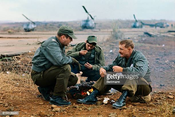 Two American and one Vietnamese soldier relax around a campfire near an airstrip containing several Bell UH1 Iroquois These men are part of Operation...