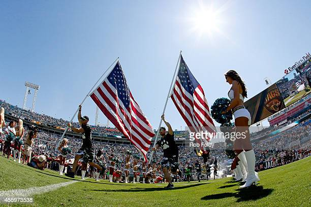 Two American Flags are carried onto the field before the game between the Jacksonville Jaguars and the Indianapolis Colts at EverBank Field on...