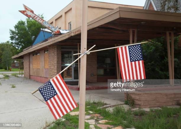 two american flags hang from a lamp post in front of an abandoned motel - timothy hearsum stock-fotos und bilder