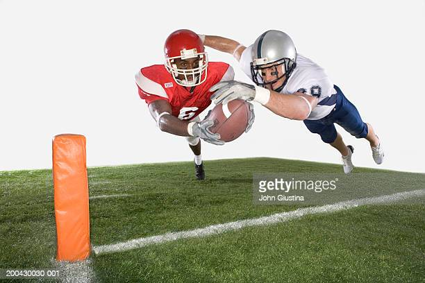Two american football players diving with ball (digital composition)