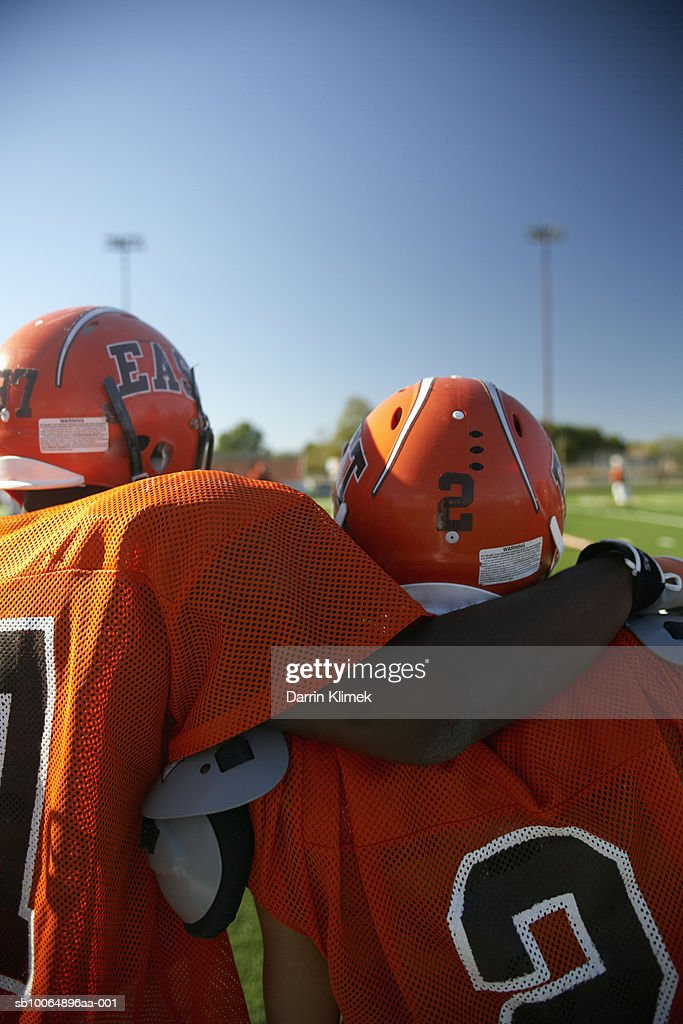 Two American football players looking at playing field, rear view : Foto de stock
