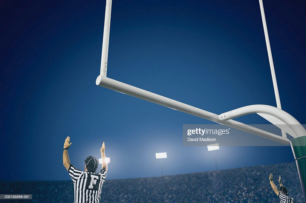 Two American football referees giving touchdown signal, rear view : Stock Photo
