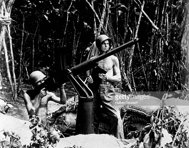 Two American Marines firing a capture .50 calibre Japanese machine gun at Japanese planes during the battle for Guadalcanal in the Solomon Islands,...