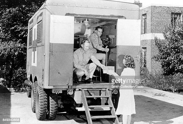 Two American Red Cross employees handing out medical supplies to a woman from a mobile unit 1958 Image courtesy CDC