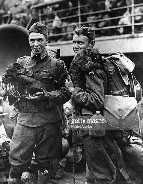 Two American soldiers about to embark for duty with their pets a dachshund and a racoon