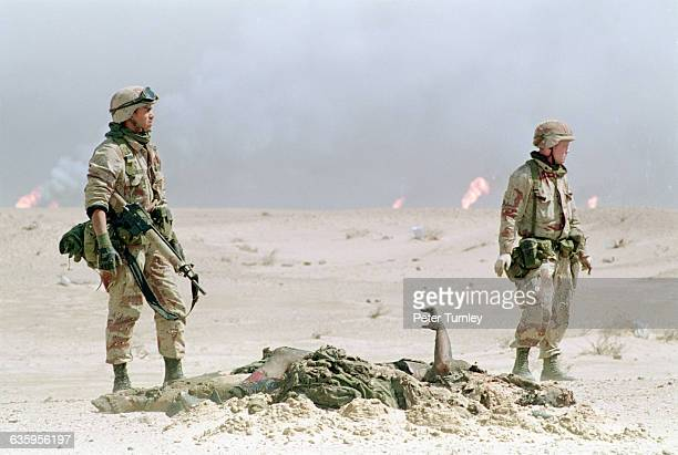 Two American soldiers wearing camouflage uniforms stand next to a dead soldier killed in the Persian Gulf War | Location Border of Kuwait and Iraq