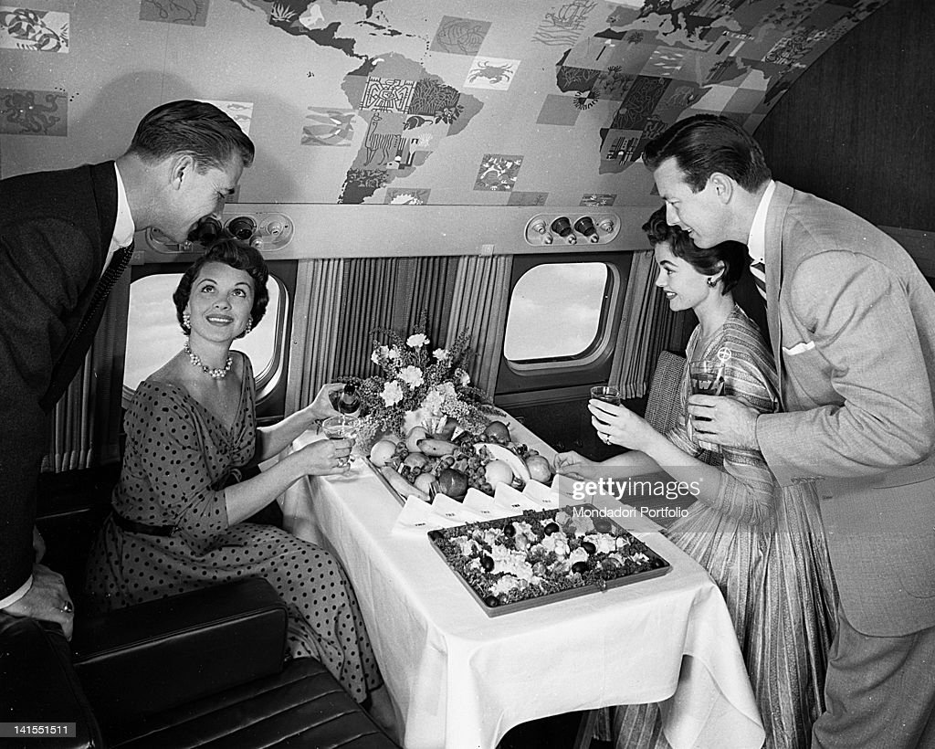 Two American women and two American men smiling in front of the buffet served on the intercontinental aeroplane 'Super G Constellation' of the airline 'TWA'. USA, 16th February 1955