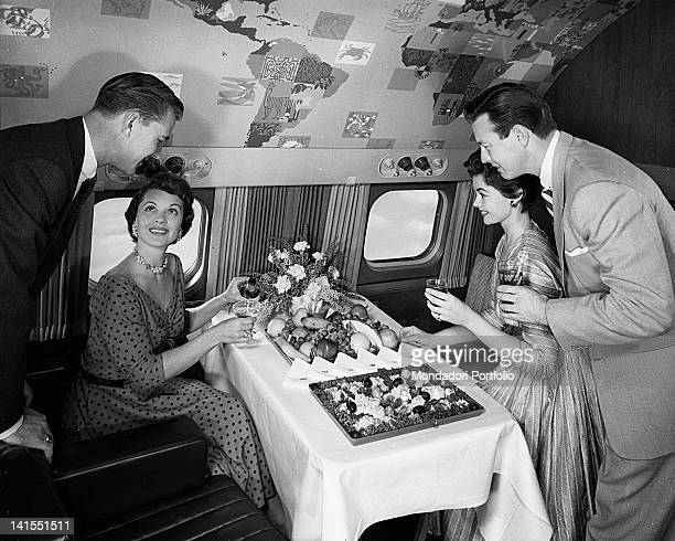 Two American women and two American men smiling in front of the buffet served on the intercontinental aeroplane 'Super G Constellation' of the...