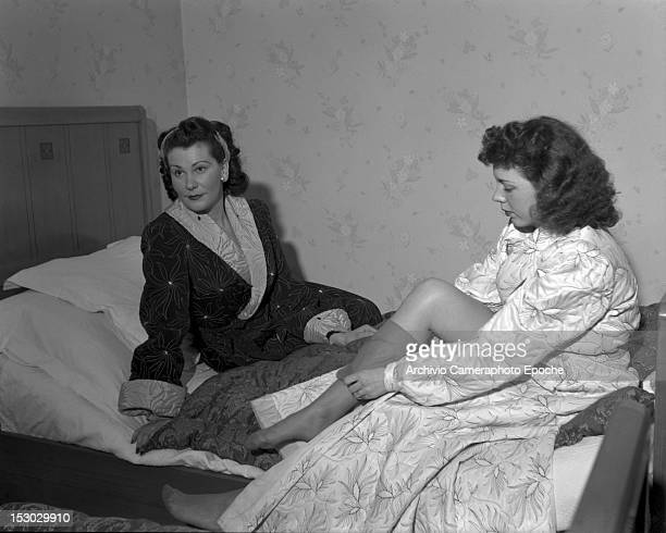 Two American young women sitting on a hotel bed in Lausanne 4th January 1949
