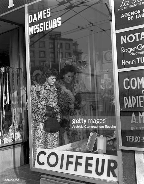 Two American young women standing outside a hairdresser window Lausanne 4th January 1949