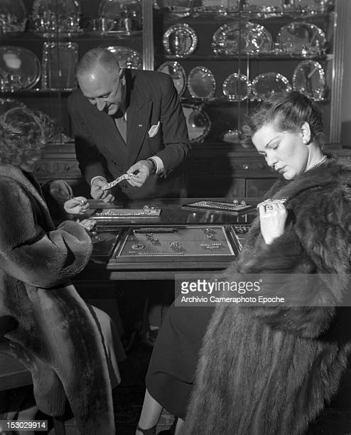 Two American young women wearing furs and trying on jewellery in Lausanne 4th January 1949