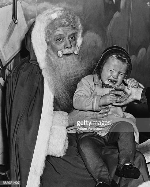 Two and a half yearold Jennifer Martin in tears during a visit to Santa at Harrods department store in London 10th December 1949