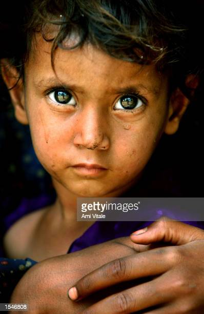 Two and a halfyearold Shuma Bibi sits in her aunt's arms in a make shift refugee camp after fleeing their village of Laliyal June 1 2002 in the...