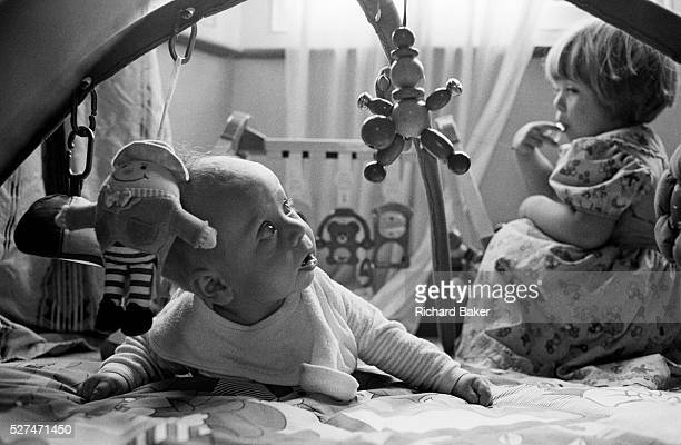 A two and half yearold girl looks over her shoulder to eye her young baby brother suspiciously while he plays on the floor with a play mobile toy It...