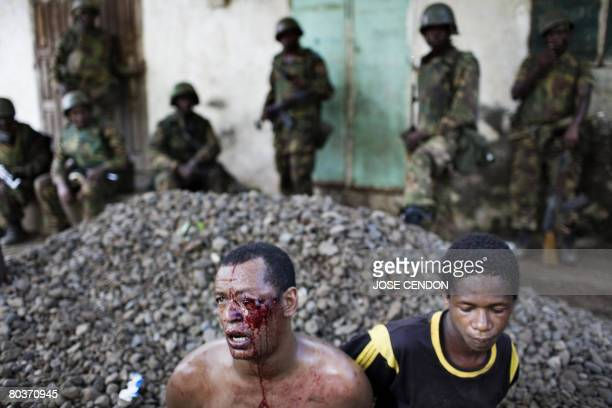 Two Anjouanese men sit on the ground after being arrested under suspicion of collaborating with renegade Anjouan leader Mohamed Bacar in Mutsamudu...