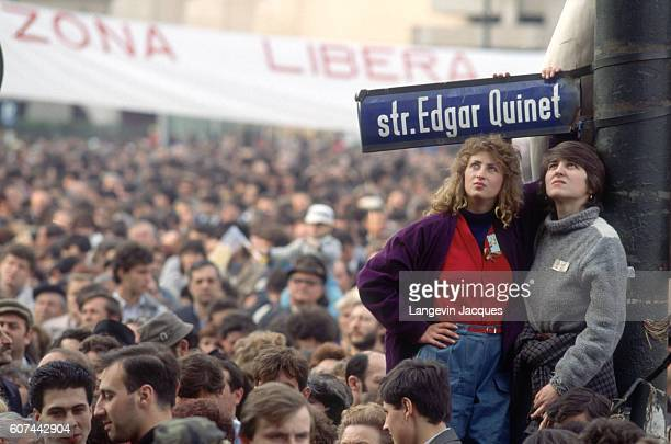Two anti-Communist protesters stand under a street sign for Edgar Quinet Street at University Square in Bucharest before the Romanian national...