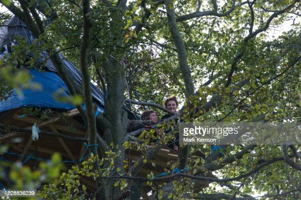 Two anti-HS2 tree protectors look down from a makeshift tree house about 60 feet above ground during evictions by National Eviction Team bailiffs...