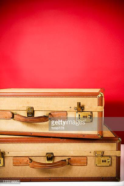 Two antique suitcases stacked  against red background