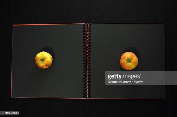 Two Apples On A Black Notebook