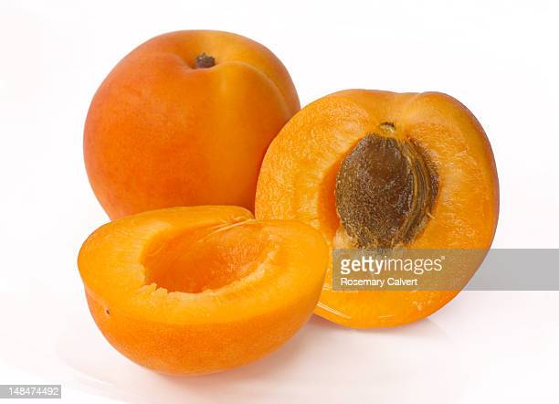 Two apricots with one cut in half to reveal stone