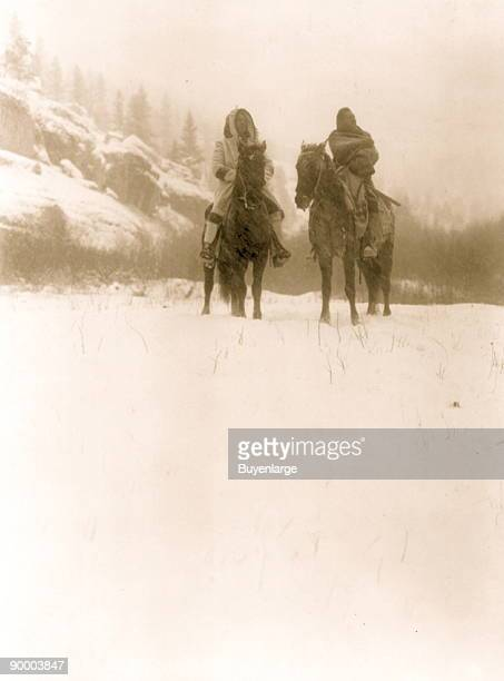 Two Apsaroke men one wearing a hooded coat the other wrapped in a blanket on horseback on snowcovered ground trees and hillside in background