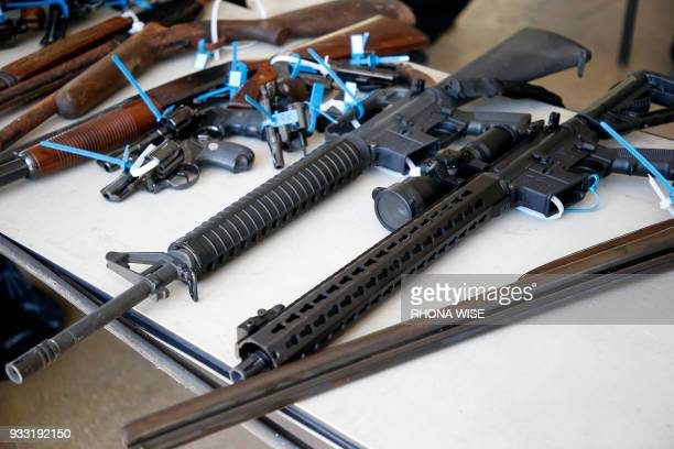 Two AR15 rifles along with other assorted guns sit on a table after being surrendered during a City of Miami gun buyback event in Miami Florida on...